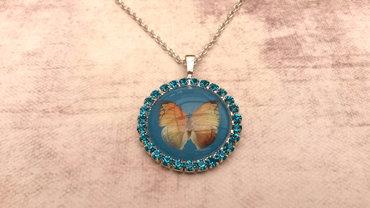 Handgemaakte ketting met blauwe strass en vlinder
